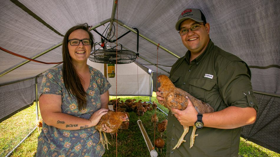 Man and woman holding chickens at their farm.