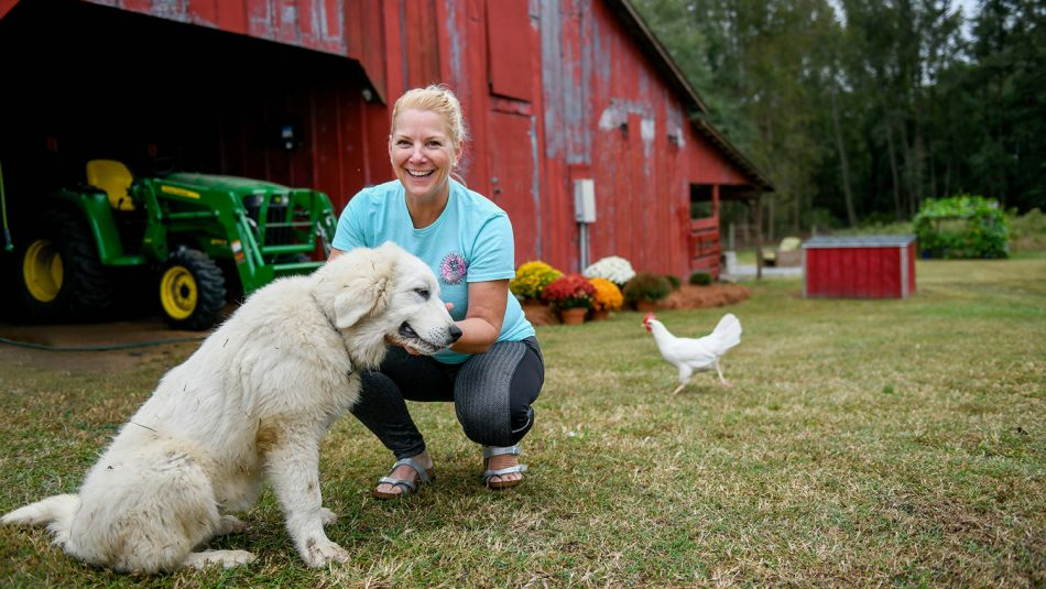 Woman smiling with her hand out to dog. In the background, a big, red barn, tractor and chicken.